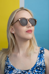 beautiful young blonde woman with elegant sunglasses posing in a