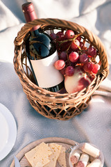Picnic background with basket, wine and fruits by the ocean