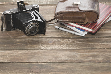 Old photocamera with leather case, notebooks on vintage wood background