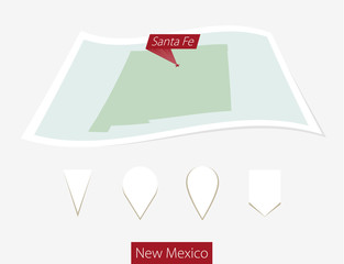 Curved paper map of New Mexico state with capital Santa Fe on Gray Background. Four different Map pin set. Vector Illustration.