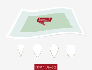 Curved paper map of North Dakota state with capital Bismarck on Gray Background. Four different Map pin set. Vector Illustration.