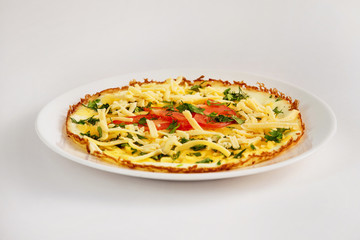 Fried eggs with cheese, tomato and parsley on a plate isolated