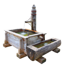 Rustical wooden well with splashing water isolated on white background. Fountain as a source drinking water. Object with clipping path.