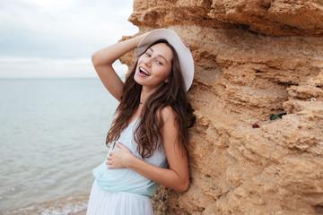 Fotobehang Happy woman standing near the rock on the beach