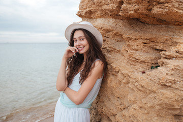 Fotobehang Cheerful cute girl standing near the rock on the beach
