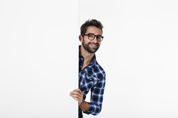 Portrait of man smiling in checked shirt, white studio
