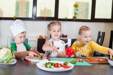 Three cute kids are preparing a salad in the kitchen