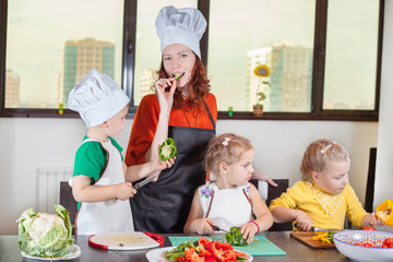 Three cute kids with mom making fruit salad