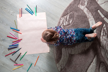 Little girl painting, drawing. Child lying on the floor near crayons. Top view. Creativity concept. Unrecognizable.