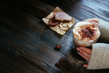female hands holding hot drink with chocolate wafers on the black table