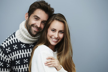 Loving couple in sweaters in studio