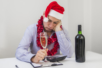 Photo Of Young Depressed Businessman Sitting In Office. Business Man Celebrate Merry Christmas And Happy New Year Wear Santa hat