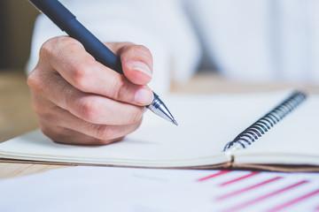 Business women hands working writing notebook on wooden desk, lighing effect
