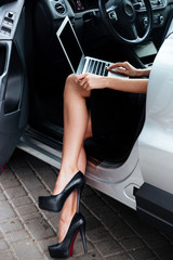 Businesswoman working on her laptop computer while sitting in ca