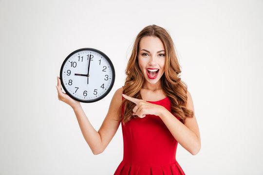 Woman in red santa claus dress pointing at wall clock