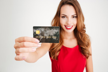 Happy attractive young woman holding and showing credit card
