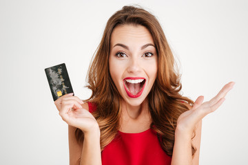 Happy excited amazed young woman holding credit card Wall mural