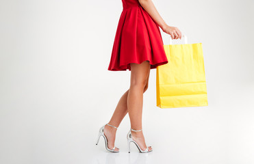 Woman in red dress and sandals holding yellow shopping bag