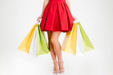 Woman in red dress and sandals holding colorful shopping bags