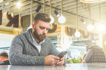 Young bearded businessman,dressed in gray cardigan,sitting at table in cafe and use smartphone. Man holding smartphone and looking at its screen. Man using gadget. Guy checking email on smartphone.