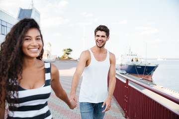Couple holding hands and walking together in port