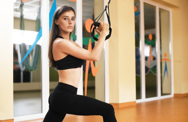 TRX. Beautiful girl in the gym doing exercices