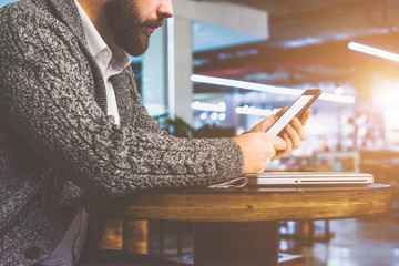 Side view of young bearded businessman in gray cardigan sits at round wooden table in cafe and use smartphone.Man holding digital gadget.Man looks at screen of smartphone. On table is closed notebook.