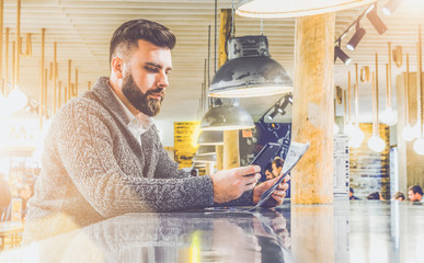 Young bearded businessman in gray cardigan sits at table in  cafe with modern interior,reading newspaper, using smartphone.From  ceiling hang lamp in an industrial style.Man checking email.