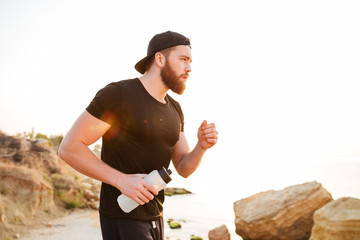 Side view portrait of a bearded sports man running outdoors