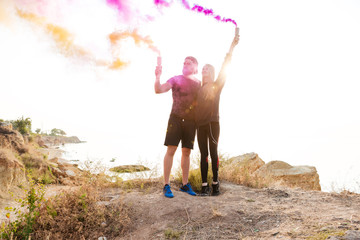 Young man and woman with smoke bombs standing at seaside