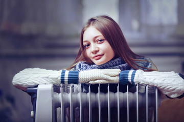 long-haired woman near electric heater at home