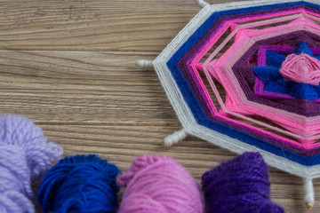 Mandala, star of woolen threads, on wooden boards with space for