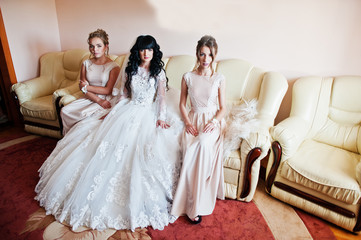 Gorgeous brunette bride with bridesmaids sitting on leather couc