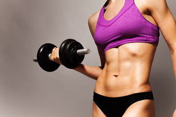 Strong fit young woman with dumbbell