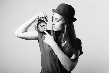 Portrait of elegant beautiful young lady in hat showing alarm clock