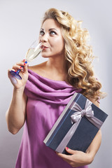 Beautiful curly-haired blond with a glass of champagne. A young woman in evening dress. Smiling girl on a gray background. Woman with gift box