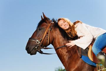 Smiling woman hugging beautiful bay horse