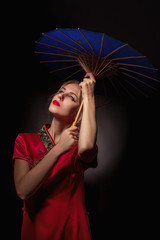 beautiful girl in asian red dress with umbrella on black background