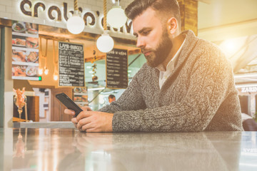 Young bearded man,dressed in gray cardigan,sitting at table of polished concrete in cafe and looking at screen of phone in his hands. Businessman using smartphone.In background,lighting and sign cafe.