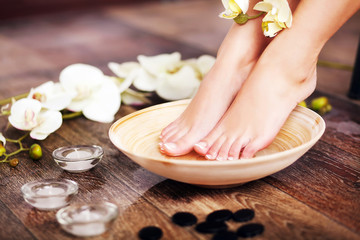 Wall Murals Pedicure Closeup photo of a female feet at spa salon on pedicure procedur