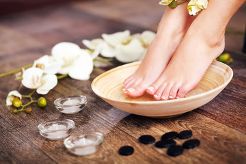 Photo sur Plexiglas Pedicure Woman washing beautiful legs in bowl, on light background. Spa p