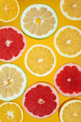 Slices of citrus fruits on the bright yellow background