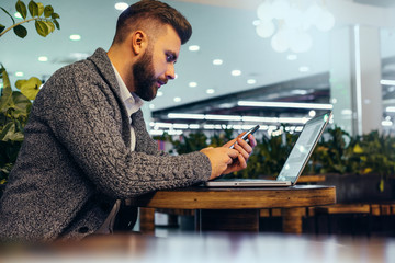 Side view of young bearded businessman,dressed in gray cardigan,sitting at round wooden table in cafe with modern interior and is holding smartphone.Laptop on table.Man uses gadget. Blurred background
