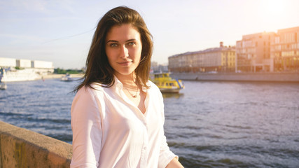 Young cute student girl with long brown hair is standing on a river background. A beautiful model look brunette woman wearing white shirt is having fun in a city park.