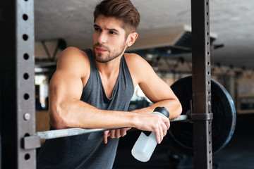 Beautiful fitness man with weights looking away