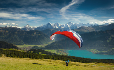 Paraglider taking off in front of spectacular Swiss scenery, Bernese Oberland, Switzerland.