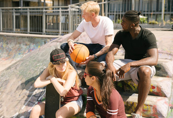 Male and female basketball friends chatting in city skatepark