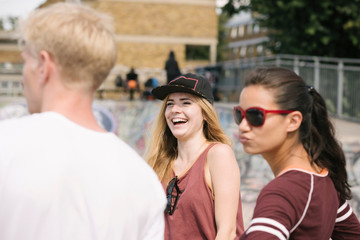Three male and female friends laughing in city skatepark