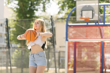 Young woman practising on basketball court