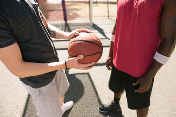 Mid section of two male basketball players with ball on basketball court